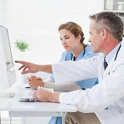male and female doctors looking at computer monitor