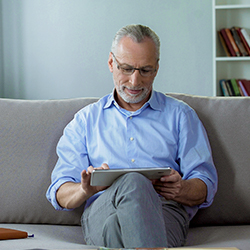 man sitting on couch using his tablet